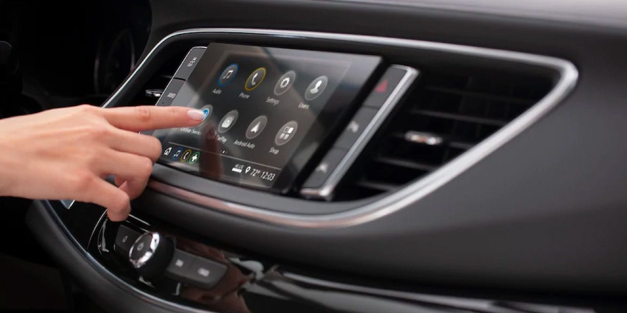 Buick Enclave Interior, driver using touchsreen display.