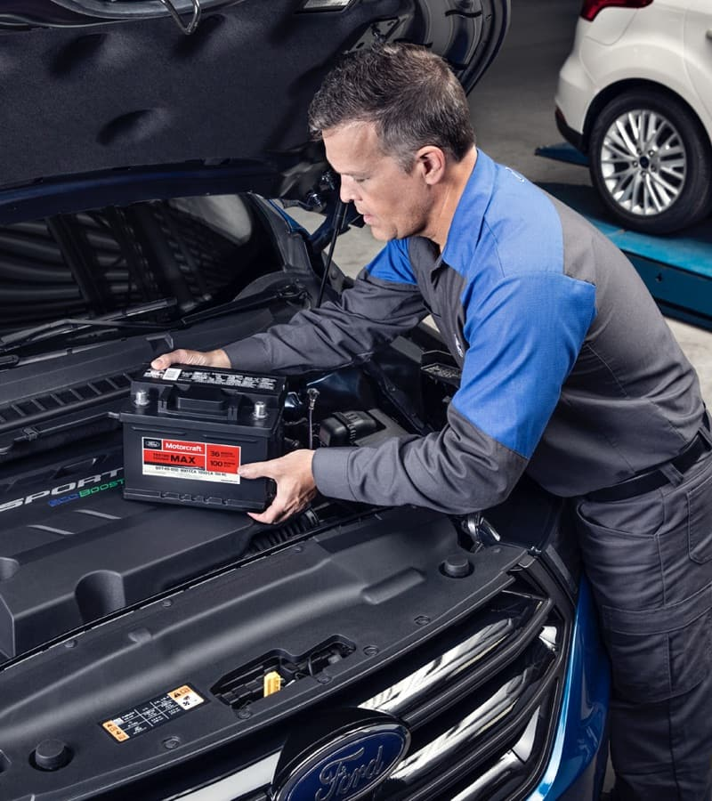 Mechanic working in engine bay of Ford vehicle
