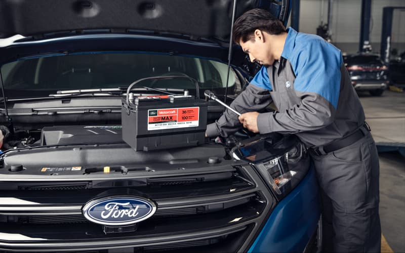 Service Tech is changing battery on a Ford vehicle.