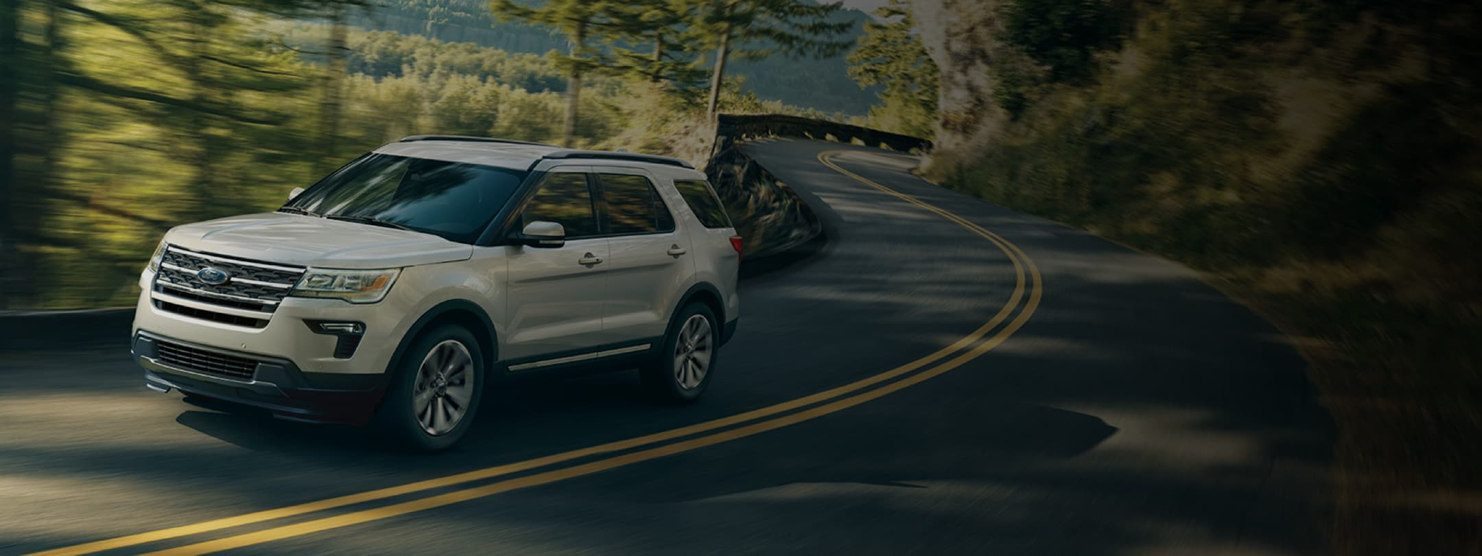 Ford SUV driving on a winding road.
