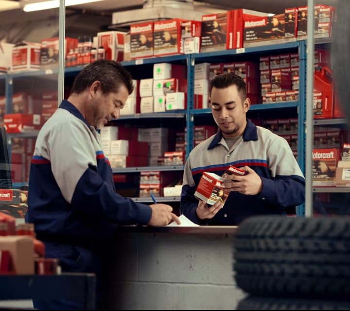 Two Parts Technicians are looking over parts in the Ford Parts Center.