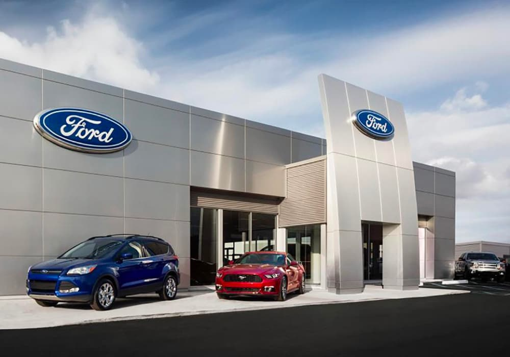 Outside of Ford Dealership, 2 New Ford Vehicles parked on the sidewalk.