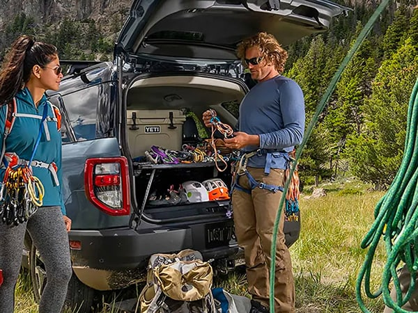 A couple gearing up for rock climbing at the back of a Ford Bronco Sport.