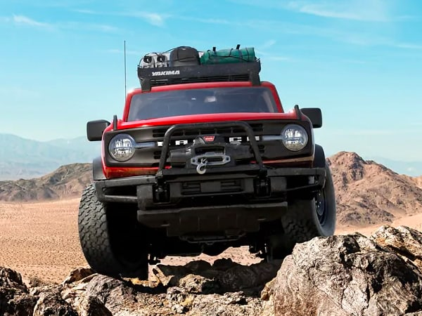 Ford Red Bronco on top of some rocks