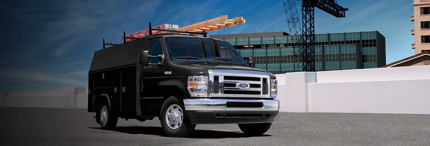 Black Ford E-Series Cutaway parked near buildings under construction
