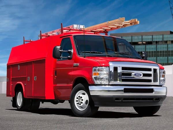 Red Ford E-Series Cutaway with a ladder on the roof
