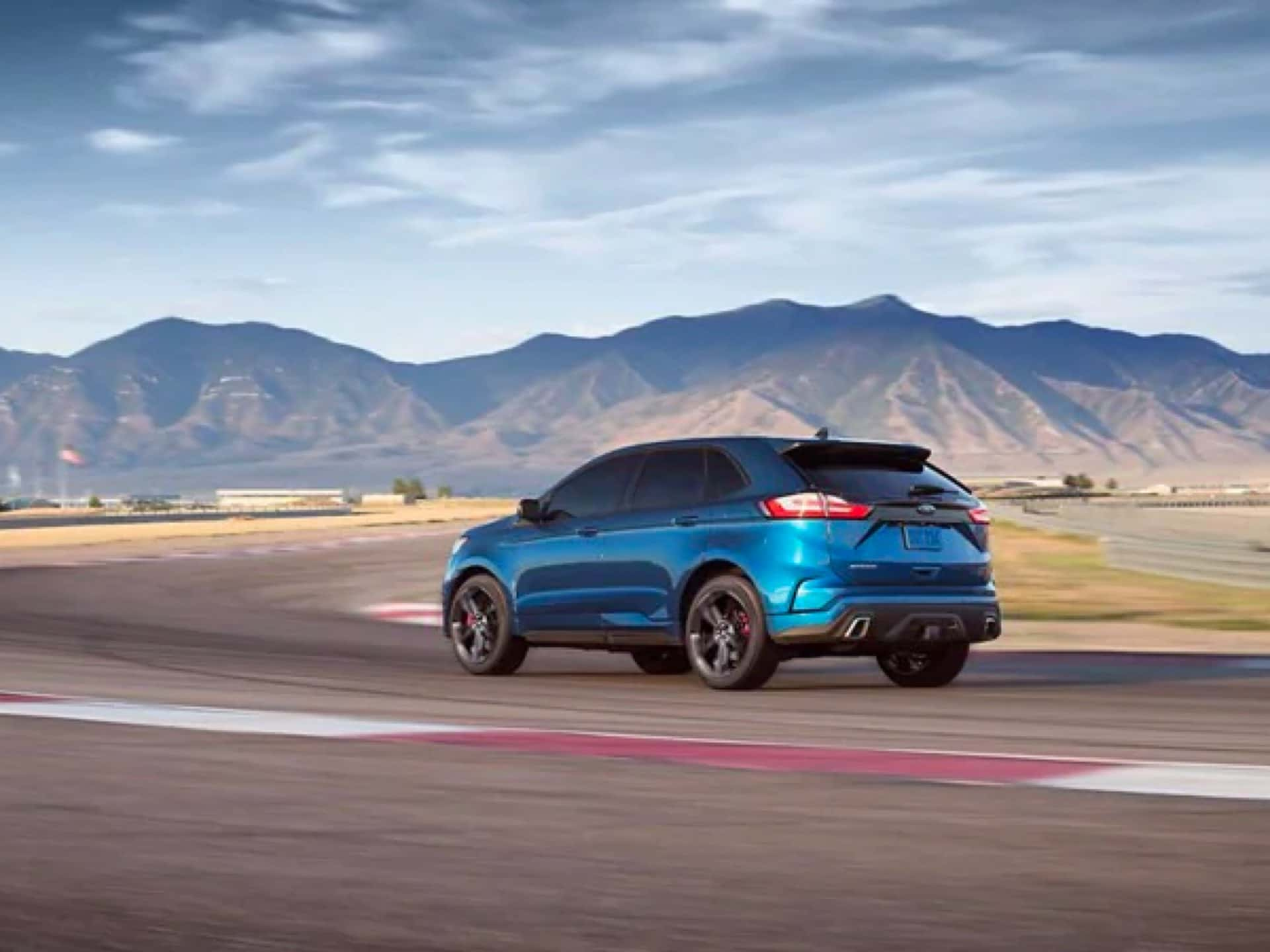Blue Ford Edge ST driving on a test track.