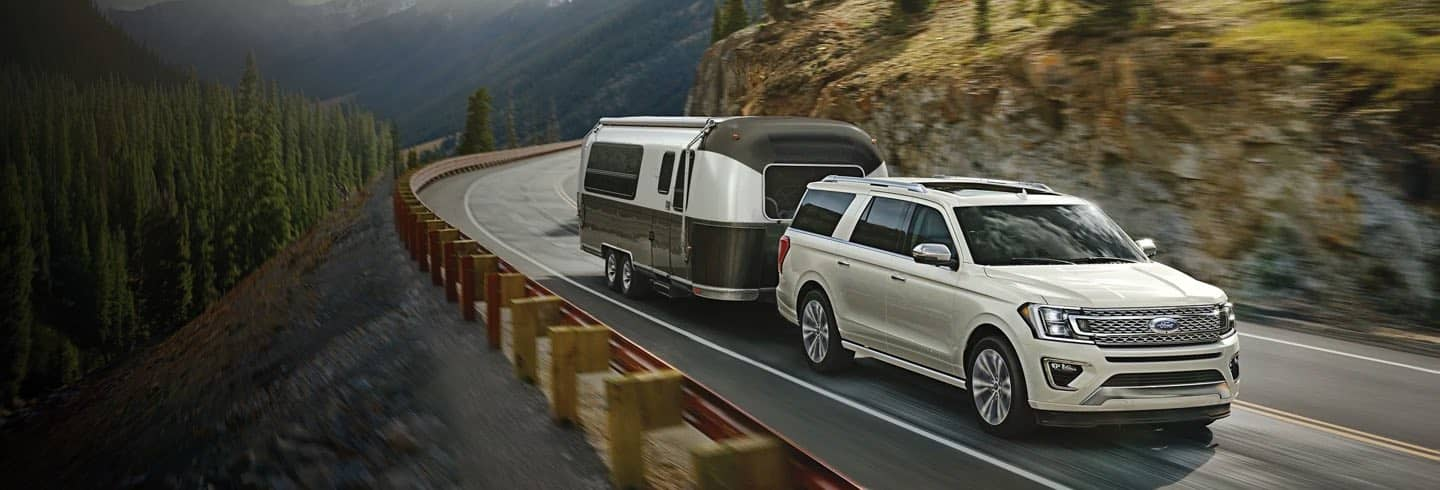 White Ford Expedition driving on a curved road towing a trailer