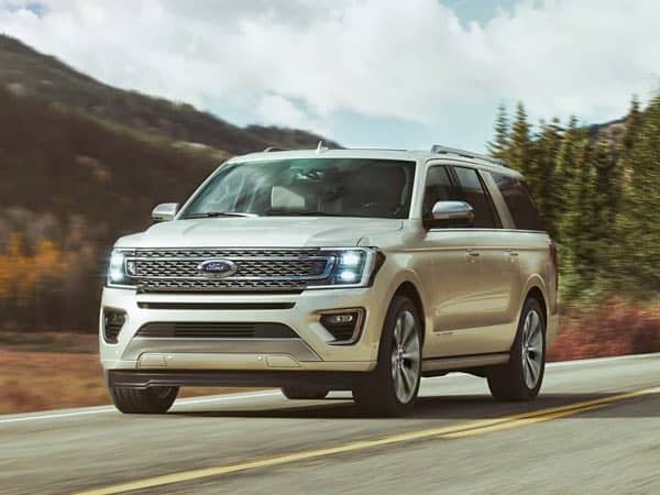 White Ford Expedition driving on a road