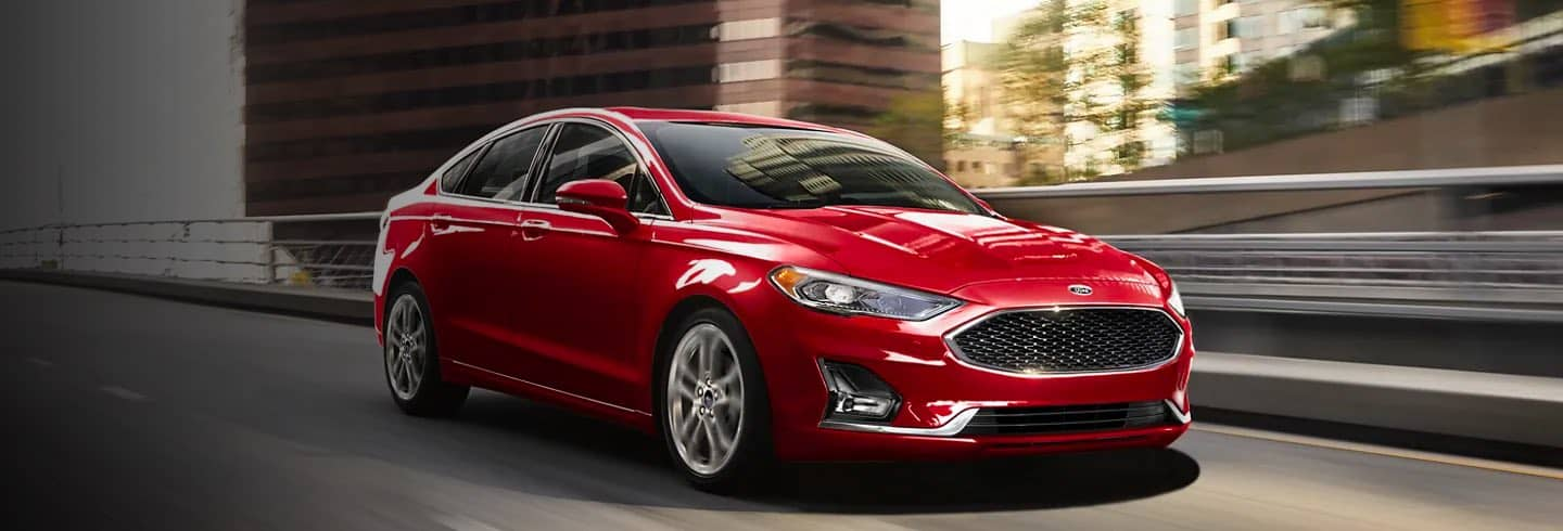 Red 2020 Ford Fusion Hybrid driving on a city street