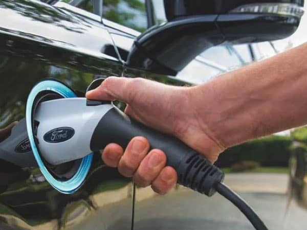 Person's hand plugging in the Ford Fusion Plug-in Hybrid
