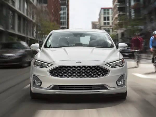 Front view of a white Ford Fusion Hybrid on a city street