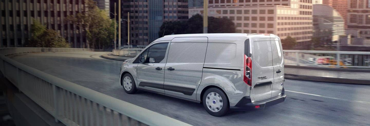 A white Ford Transit Connect Cargo Van driving on a city street.