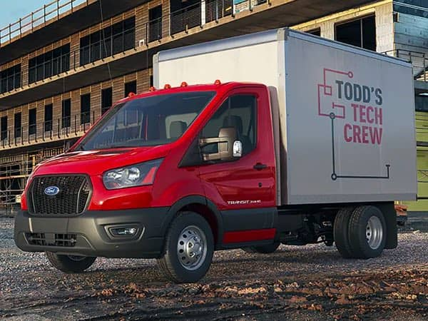 Red Ford Transit truck parked in front of a building under construction