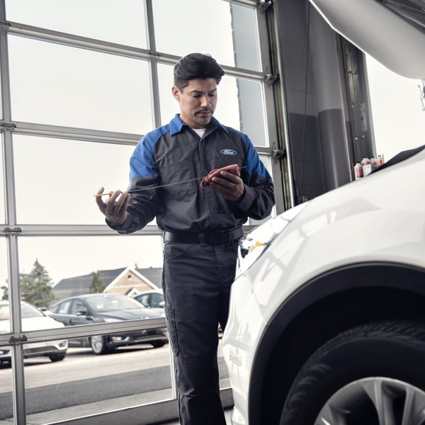 Ford service technician inspecting fluid levels