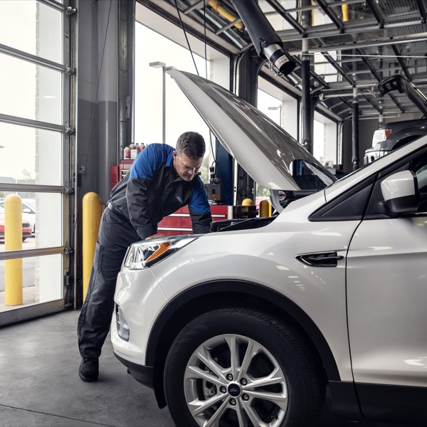 Ford service technician working on engine