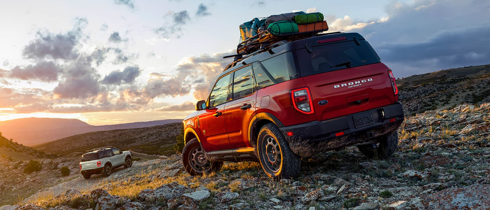 SUVs driving over rough terrain into the sunset