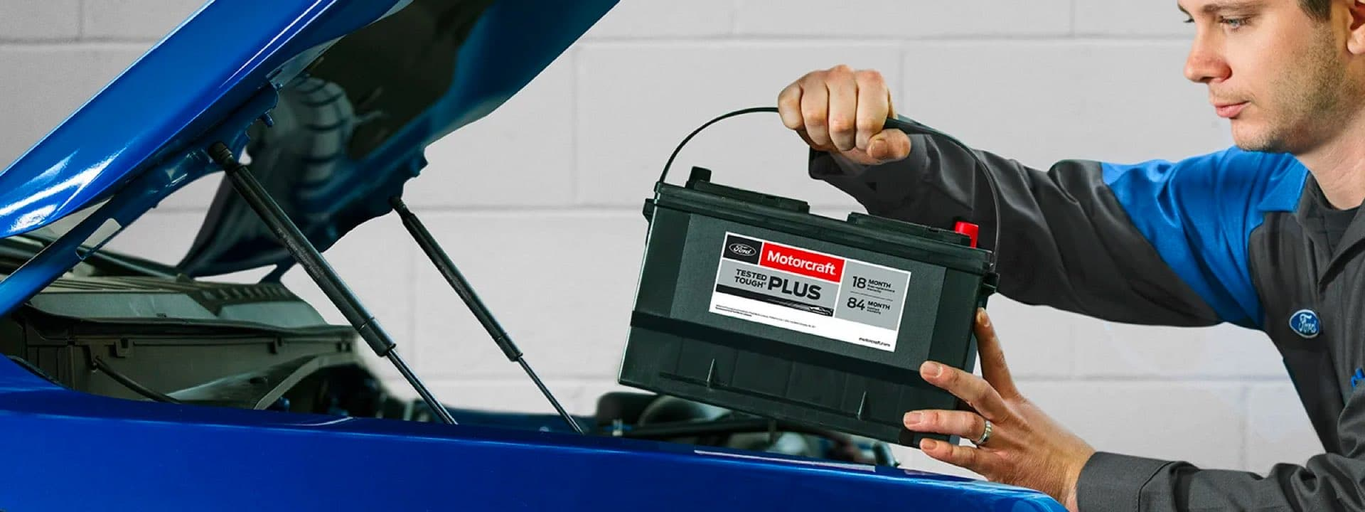 Technician placing new battery in car