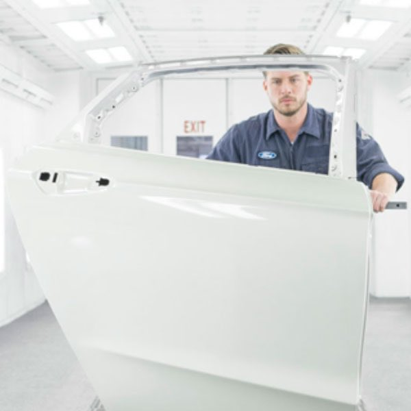 Ford collision repair technicial painting a door