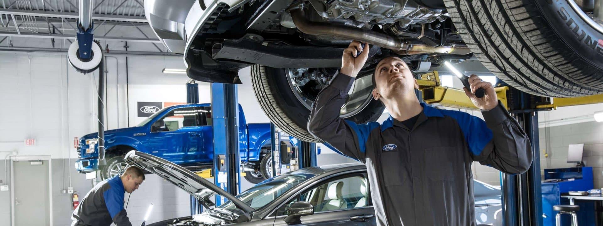 Technician looking at underside of car