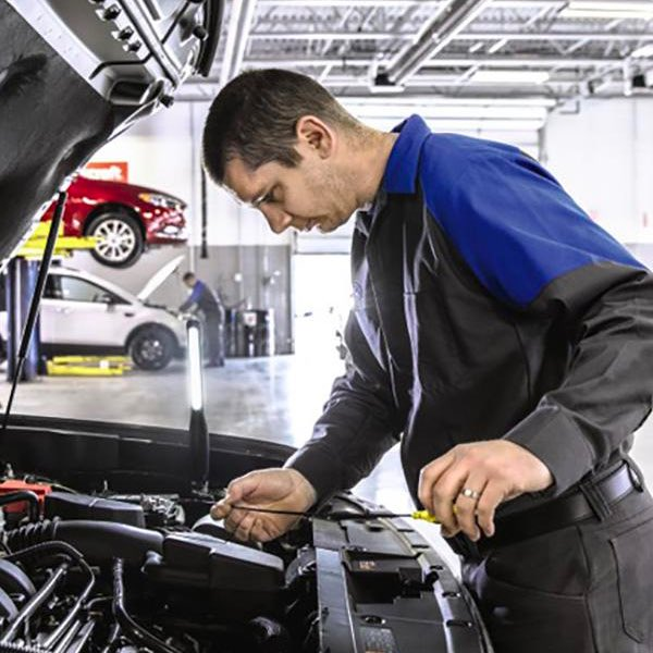 Technician servicing vehicle under the hood