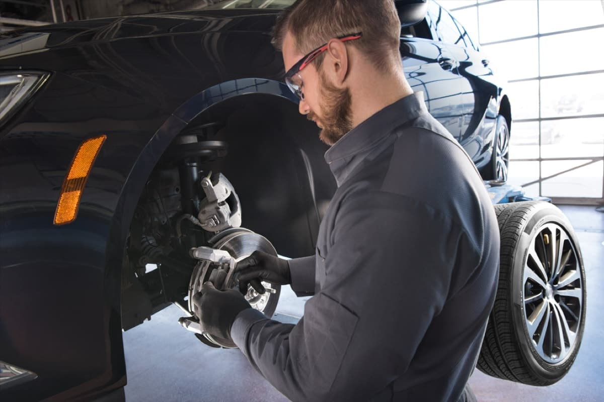 A service technician repairing brakes