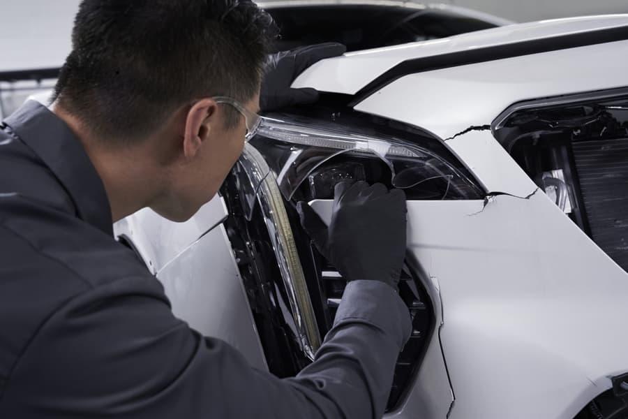 Technician working on damaged vehicle
