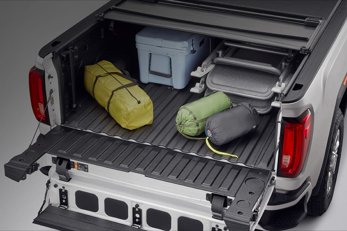 A GMC trunk filled with accessories & floor mats