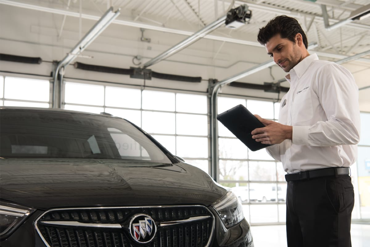 A sales guy looking at his ipad, while standing next to a Buick vehicle