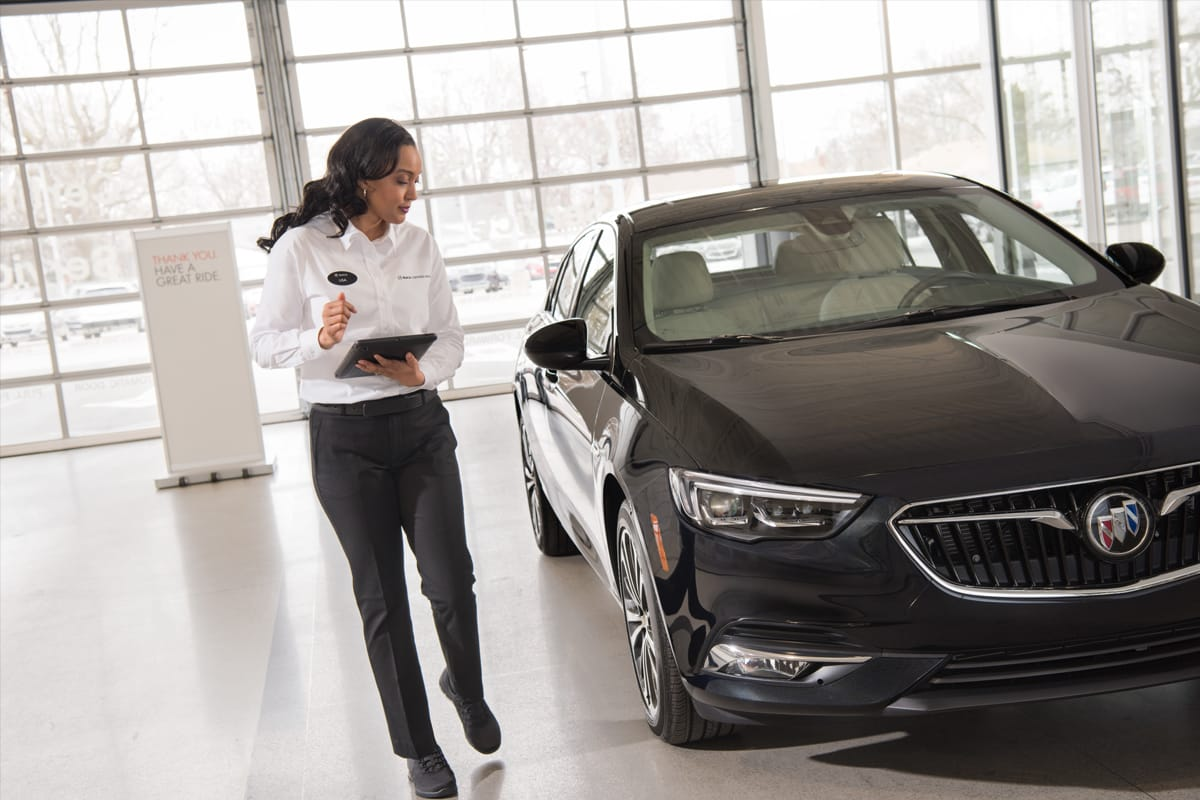 Service tehnician looking and inspecting a Buick vehicle