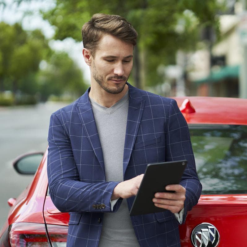 A man looking at his iPad behind a Buick red car.