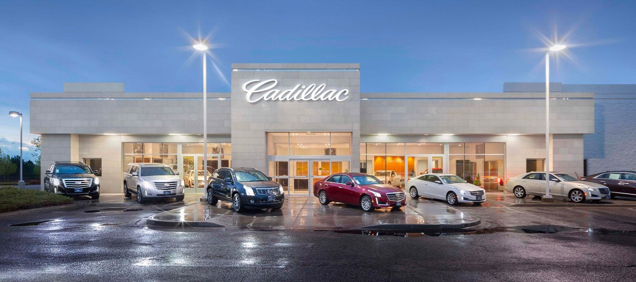 An exterior shot of a Cadillac dealership at night.