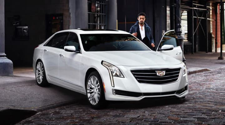 A man is getting into his white Cadillac sedan