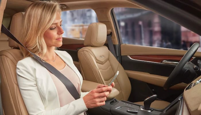 A woman sitting on the passenger seat, looking at her phone