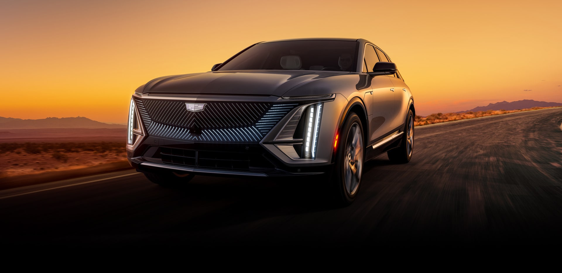2023 Cadillac Lyriq driving at sunset