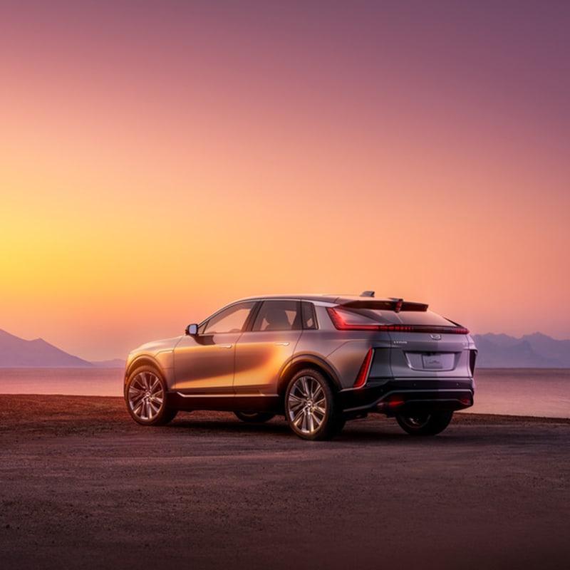 2023 Cadillac Lyriq parked on a beach at sunset