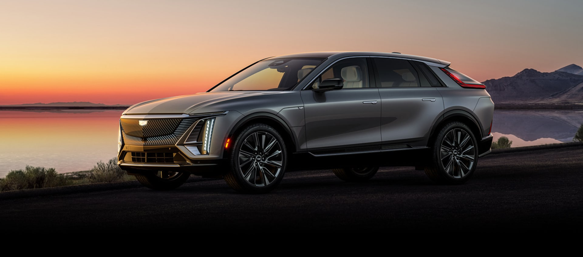 2023 Cadillac Lyriq parked near a mountain lake
