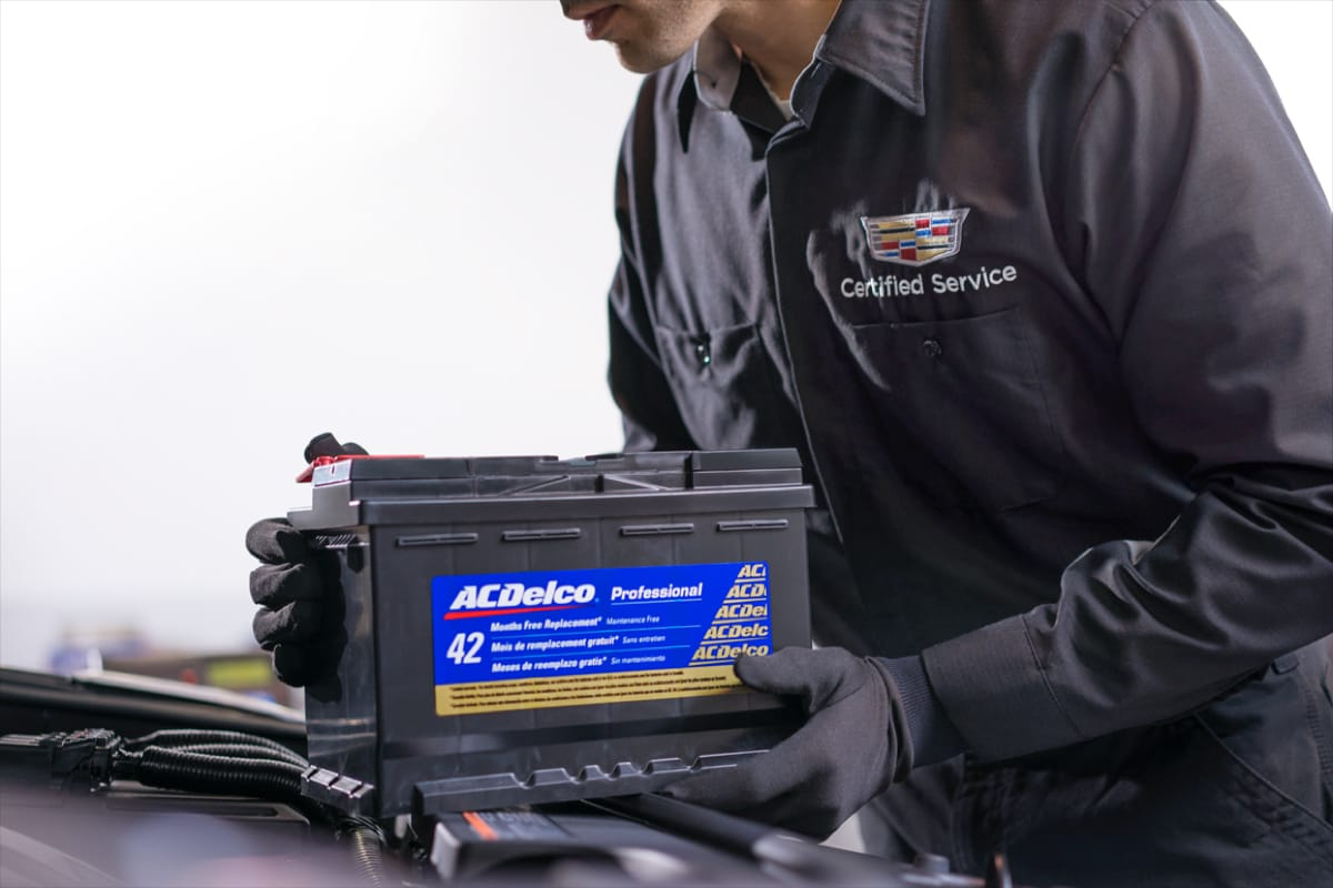 A closeup shot of a service technician's hand replacing a car battery