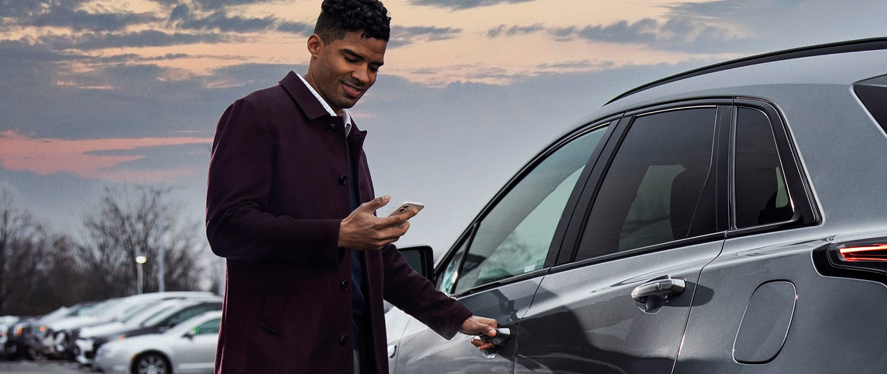 A guy at the driver door, with his hand on the door handle, using his phone.