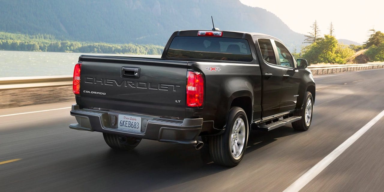Rear view of 2021 Chevrolet Colorado driving down road with lake and mountain in background,