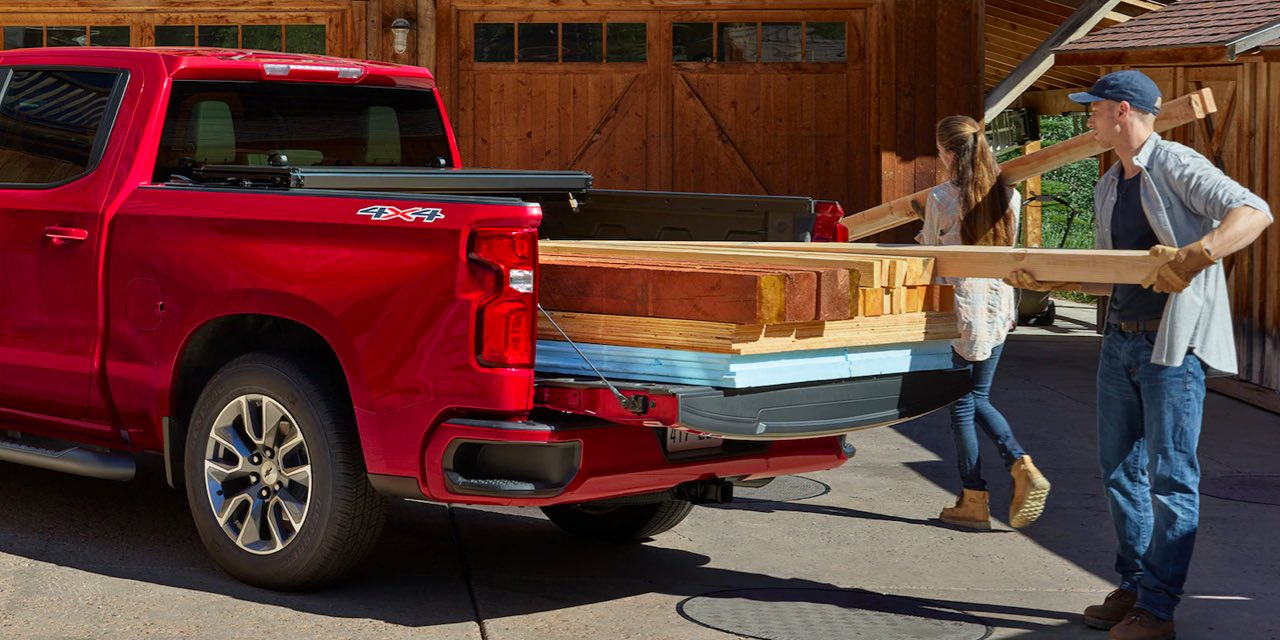 Red 2021 Chevrolet Silverado being loaded with lumber