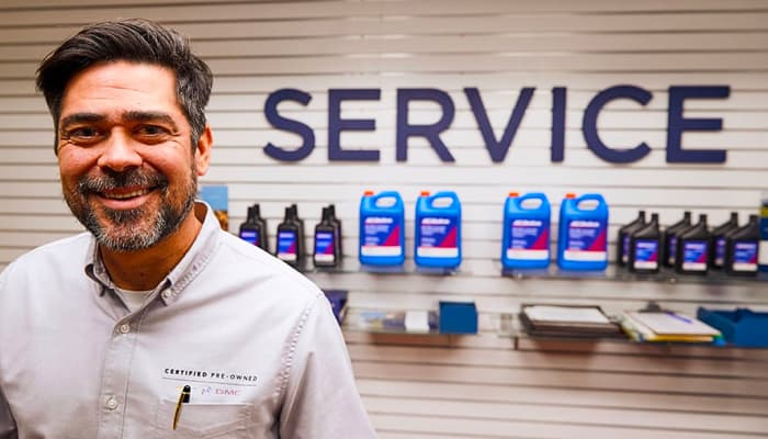 A mechanic smiling in front of service products display.