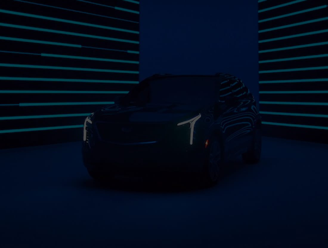 A Cadillac SUV parked inside a room with neon lights