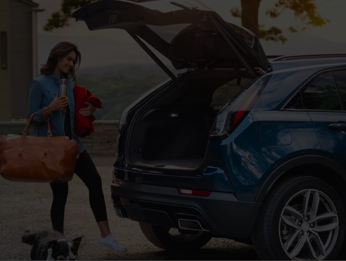 A girl holding a lot of things, and using her foot to open up the trunk.