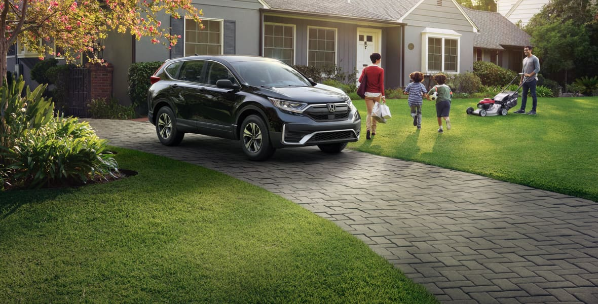 A black Honda SUV is parked in a driveway. A mother and two children are walking inside their house while the father mows the lawn.