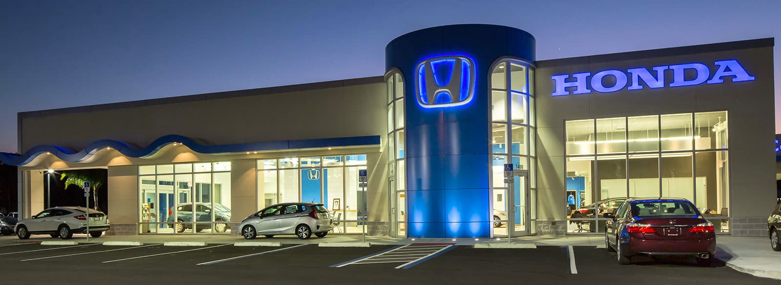 An exterior shot of a Honda dealership at night.