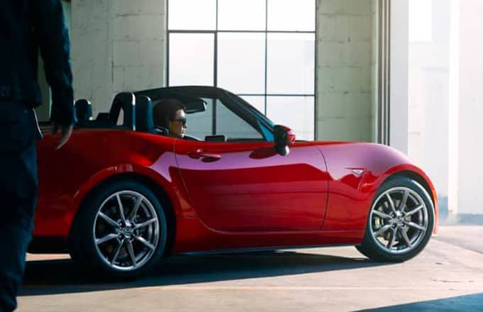 A red Mazda convertible is driving out of a garage