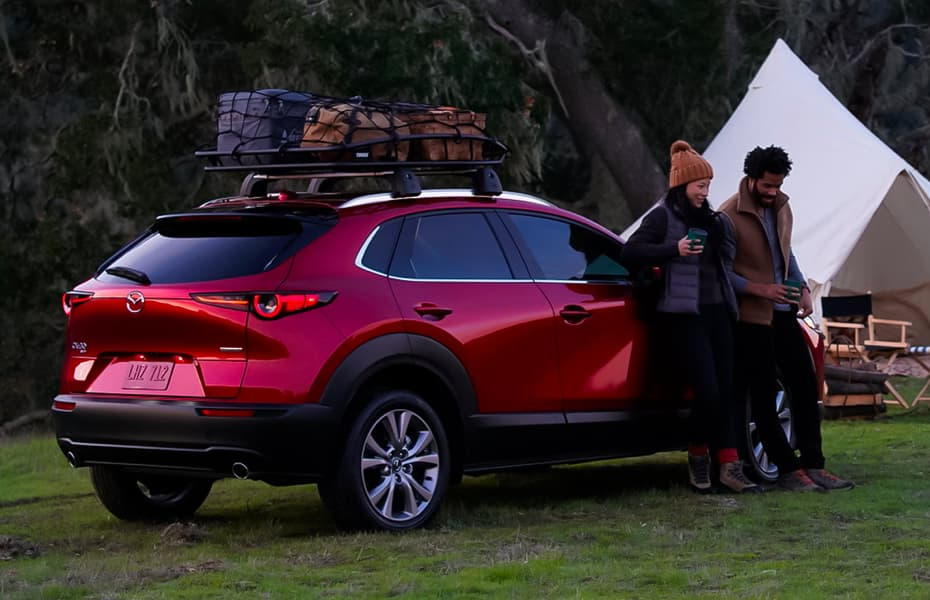 Couple are camping and are outside leaning against a brand new red Mazda SVU.