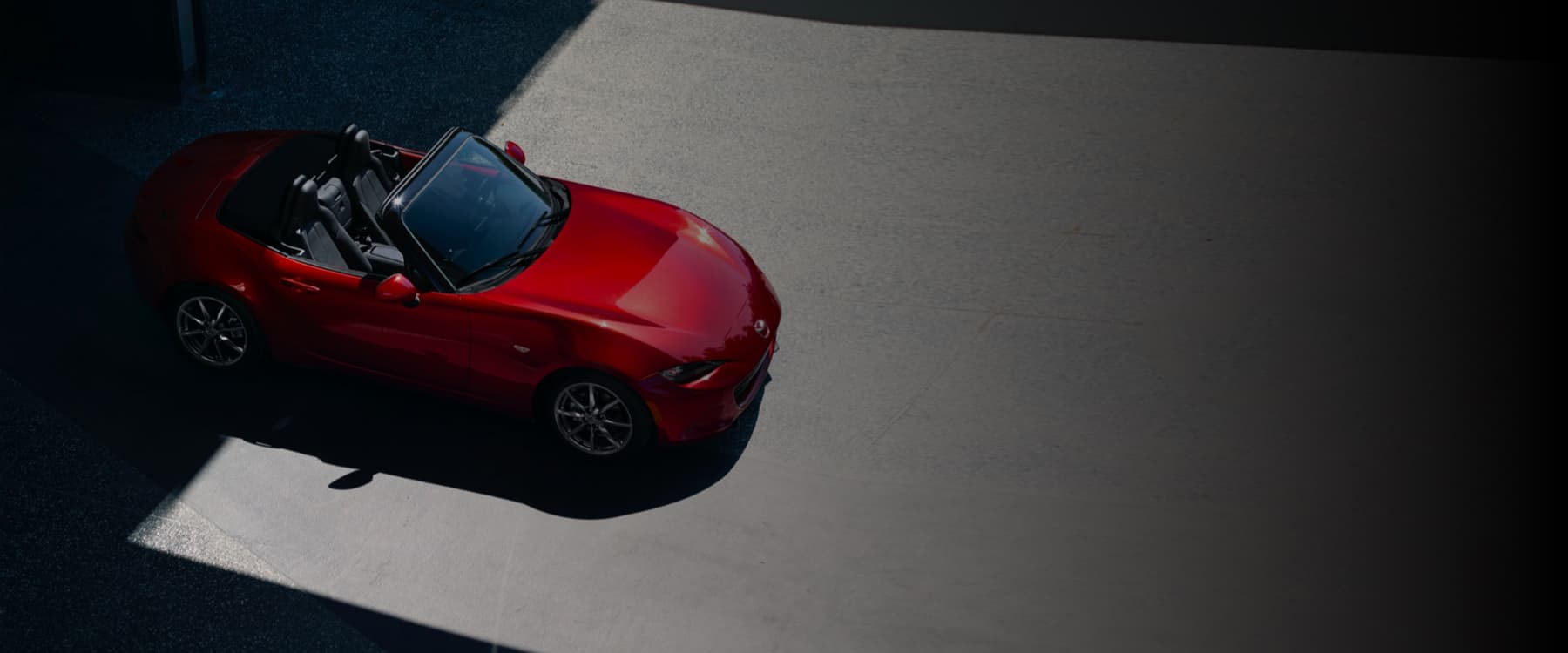 Red Mazda convertible being driven outside.