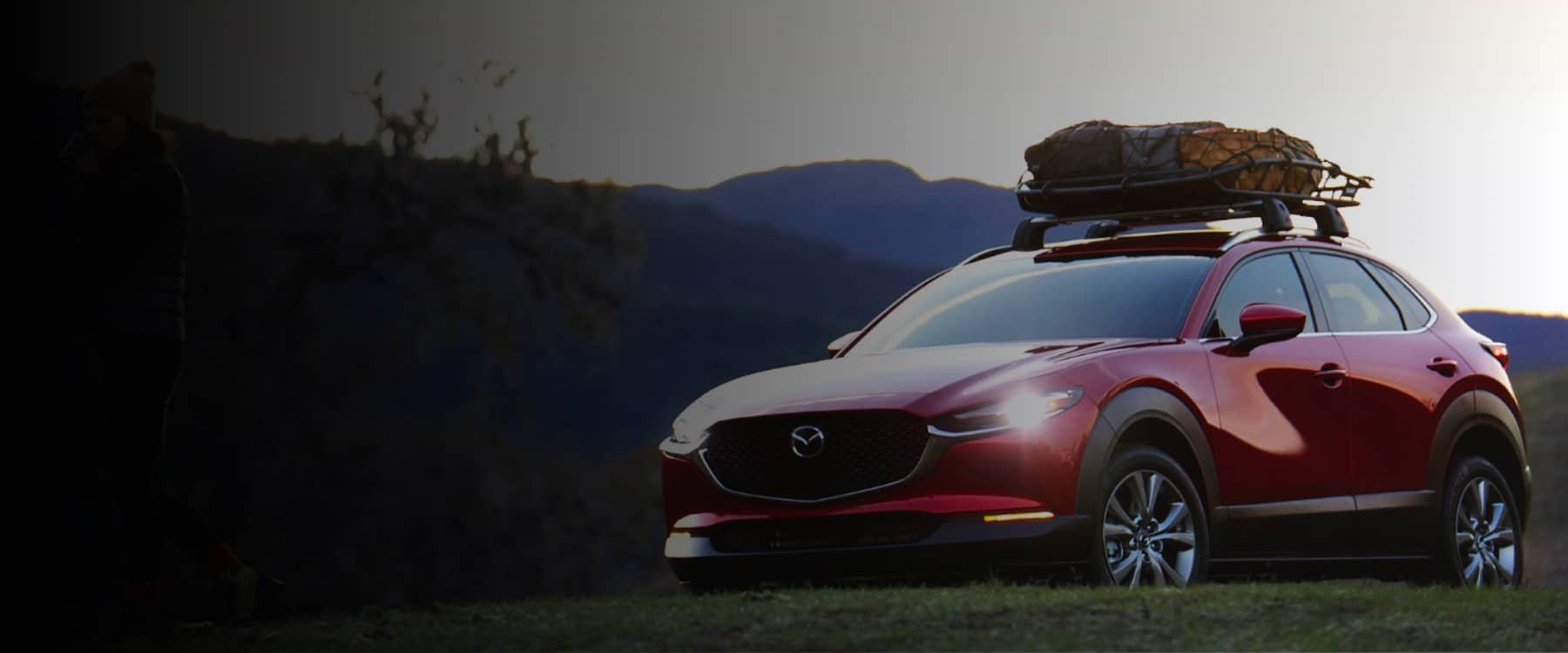A red Mazda SUV with a cargo carrier against a mountainous backdrop.